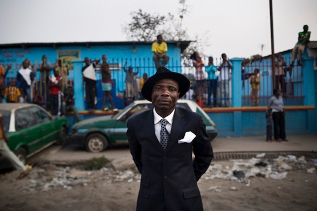 SAPE: Society of Ambianceurs and Elegant People At the beginning of the XXth century when the French arrived in Congo the myth of the Parisian elegance was born among the youth of the Bakongo ethnic group who were working for the colonizers. At that time the white man was considered superior, someone showing better manners and elegance. The legend says that in 1922 Grenard André Matsoua, who was an important political activist, was the first Congolese ever to come back from Paris dressed as a genuine French. His arrival caused indescribable commotion and admiration among his fellow countrymen and he became known as the first Grand Sapeur. Having the respect and admiration of his community, today's Sapeurs consider themselves artists. They add a touch of glamour to their humble environment through their refined manners and impeccable dressing styles. Each of them is unique showing a particular repertoire of gestures. They all share the same dream: To go to Paris and return to Brazzaville as an aristocrat of supreme elegance.